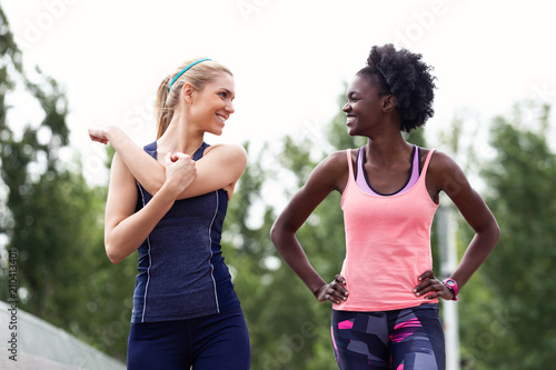 Two sporty young women talking and relaxing after running in the city.