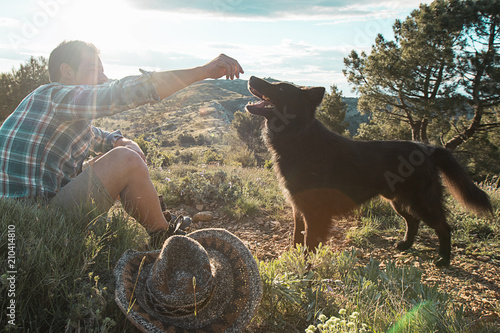 Guy playing with his dog at sunset