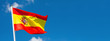 Leinwandbild Motiv Flag of Spain waving in the wind on flagpole against the sky with clouds on sunny day, banner, close-up