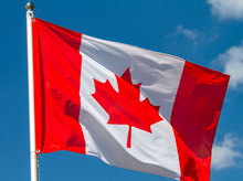 Flag Of Canada Waving In The Wind On Flagpole Against The Sky With Clouds On Sunny Day, Close-up