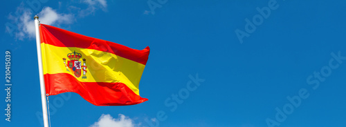 Fotografía  Flag of Spain waving in the wind on flagpole against the sky with clouds on sunn