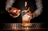 Barman making a fresh and tasty old fashioned cocktail with orange peel and smoke note