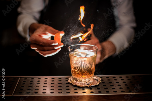 Photo sur Toile Cocktail Barman making a fresh and tasty old fashioned cocktail with orange peel and smoke note
