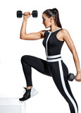 Fitness girl performs exercising with dumbbells for hands. Photo of sporty girl in black fashionable sportswear isolated on white background. Strength and motivation.