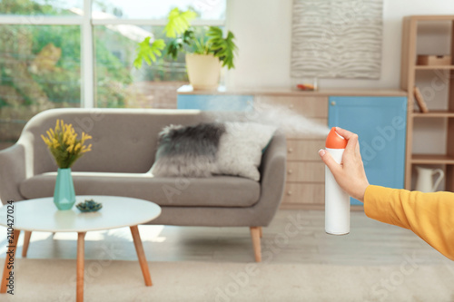 Fototapeta Woman spraying air freshener at home obraz