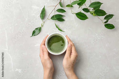 Woman with cup of matcha tea and leaves at table, top view