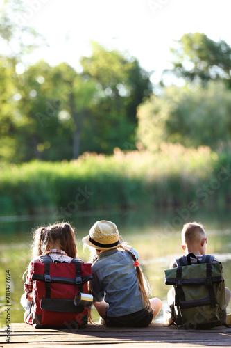 Obraz Little children sitting on wooden pier. Summer camp - fototapety do salonu