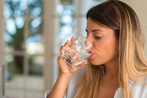 Fotografiet Beautiful young woman drinking a glass of water at home
