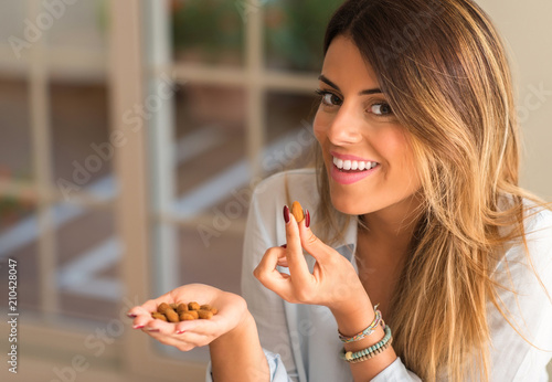 Fototapeta Beautiful young woman smiling and eating nuts at home. Healthy concept. obraz