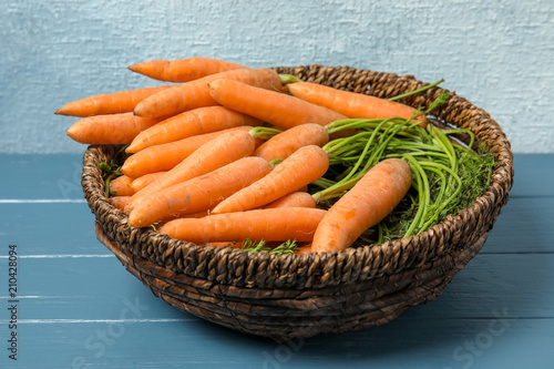 Bowl with ripe carrots on wooden table