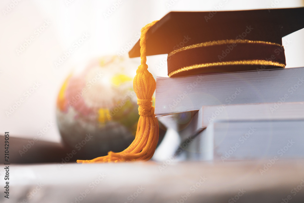 Fototapeta Graduated or Graduation university study abroad international Conceptual, Master cap on books stack with blur of america earth world globe model map in Library room of campus, Back to School
