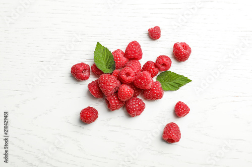 Ripe aromatic raspberries on wooden table, top view