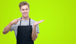 Leinwanddruck Bild - Young handsome blond man wearing apron very happy pointing with hand and finger