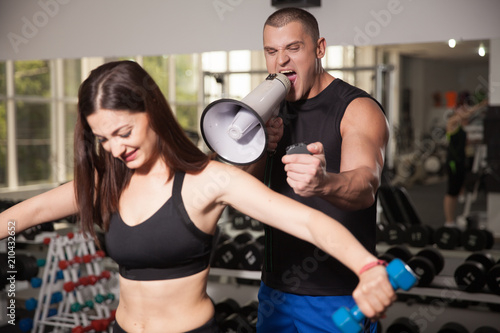 Spoed Foto op Canvas Fitness Personal trainer. Development of methods of weight loss. Fitness instructor. Restoration of the figure after childbirth. Exercises in the gym.