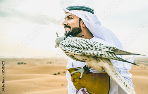 plakat Arabic man with traditional emirates clothes walking in the desert with his falcon bird