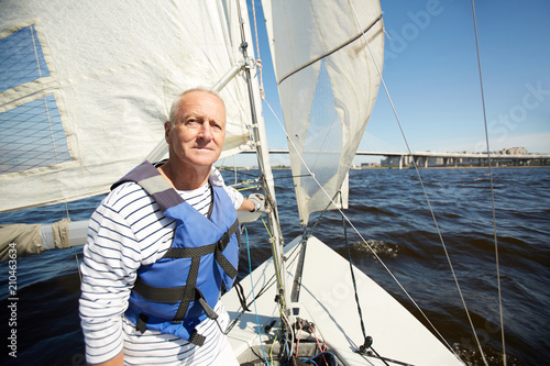 Senior man in lifejacket sitting in yacht and enjoying summer weekend by seaside