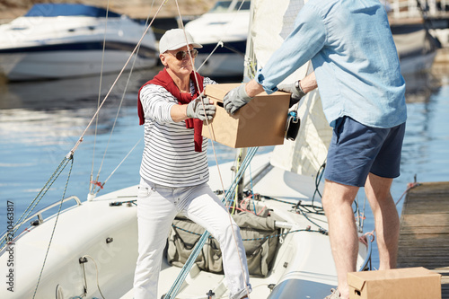 Senior man taking packed box from assistant while preparing for sea trip on yacht