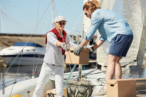 Senior yachtsman and his assistant loading boxes on boat before sailing trip on summer weekend
