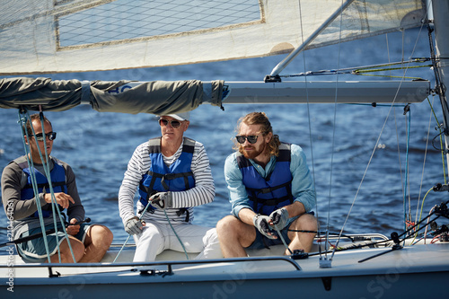 Team of three active men in lifejackets sitting in yacht while sailing in the sea