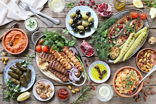 Fotografija Middle eastern, arabic or mediterranean dinner table with grilled lamb kebab, chicken skewers  with roasted vegetables and appetizers variety serving on wooden outdoor table