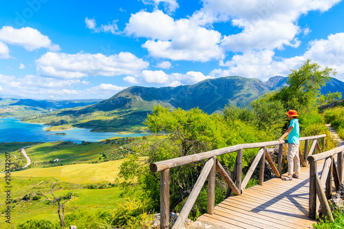 Fotografia, Obraz Young woman tourist standing on bridge near castle tower on hiking path in Zahar