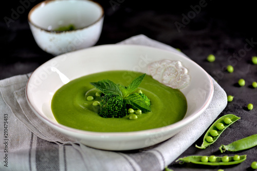 Healthy cream soup of fresh green peas with broccoli and mint