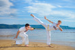 A man and a woman train capoeira on the beach.