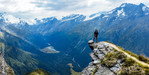 Fotografia  traveler standing at the edge of a cliff with a valley in the distance