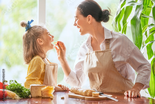 Fototapeta Mother and daughter cutting bread and cheese obraz