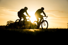 Early Morning Cyclists Silhouetted At Sunrise In Richmond Park, London