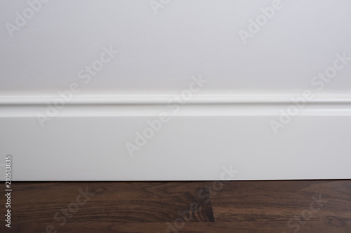 Light matte wall, white baseboard and tiles immitating hardwood flooring Canvas Print