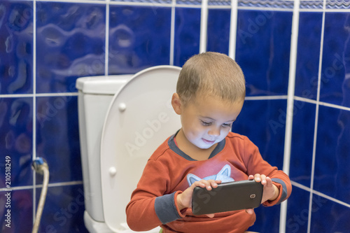 Little boy sitting on the toilet in the bathroom at home with using a smartphone Wallpaper Mural