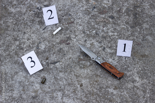 Fotografie, Obraz  Folding knife, cigarette butt and sleeve from the gun, on the concrete floor, in