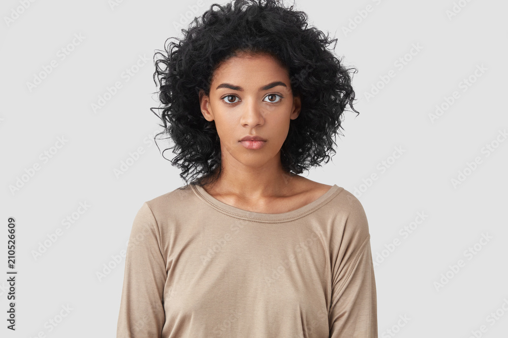 Fototapety, obrazy: Indoor shot of serious dark skinned female freelancer has Afro hairstyle, pleasant appearance, dressed in beige casual sweater, works distantly at home, enjoys domestic atmosphere. Ethnicity concept
