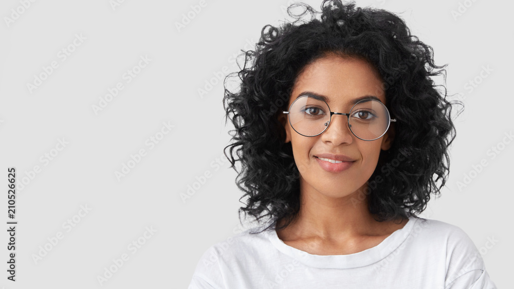 Fototapeta Close up portrait of curly female adult has charming smile, curly dark hair, wears big glasses, satisfied as finished domestic work earlier, being successful designer or architect, has talent