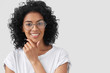 Positive African American female smiles broadly, holds chin, being self confident, presents project work in front of colleagues, wears glasses, isolated over white background. People, ethnicity