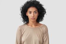 Indoor Shot Of Serious Dark Skinned Female Freelancer Has Afro Hairstyle, Pleasant Appearance, Dressed In Beige Casual Sweater, Works Distantly At Home, Enjoys Domestic Atmosphere. Ethnicity Concept