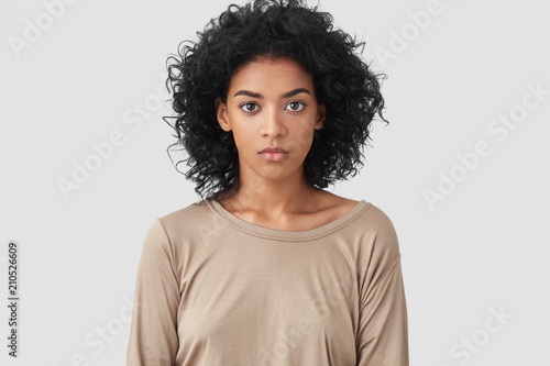 Canvastavla  Indoor shot of serious dark skinned female freelancer has Afro hairstyle, pleasant appearance, dressed in beige casual sweater, works distantly at home, enjoys domestic atmosphere