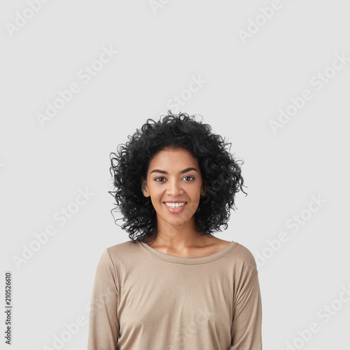 Smiling delighted young African American female has gentle smile, has white teeth, rejoices meeting with colleagues, dressed in casual clothes, isolated over white background with blank space Wall mural