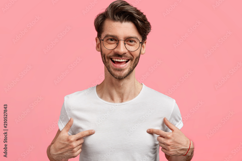 Fototapeta Horizontal shot of handsome cheerful hipster male indicates at white t shirt, shows blank space for your logo, being in high spirit, isolated over pink blank wall. Positive emotions and advertisement