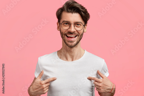 Photo Horizontal shot of handsome cheerful hipster male indicates at white t shirt, shows blank space for your logo, being in high spirit, isolated over pink blank wall