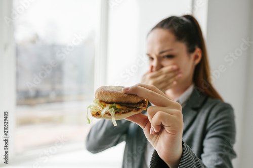 Fotografie, Tablou  A young girl shows that she does not like a burger