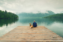 Man With Dog Sitting At Wooden Pier At Bohinj Lake, SLovenia
