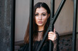 city portrait. sad girl. brunette in a black dress. expectation. dreams. portrait of a young, beautiful girl. The brunette in a black dress is standing near the cage with black rods. clings to them.