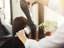 Hairdresser Drying Woman's Hair In Beauty Salon