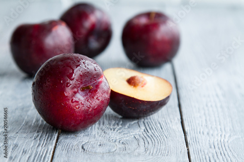 plums on wooden background with a glass of wine