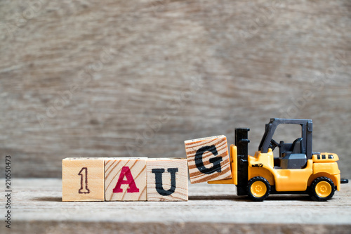 Fényképezés  Toy forklift hold block G to complete word 1 aug on wood background (Concept for