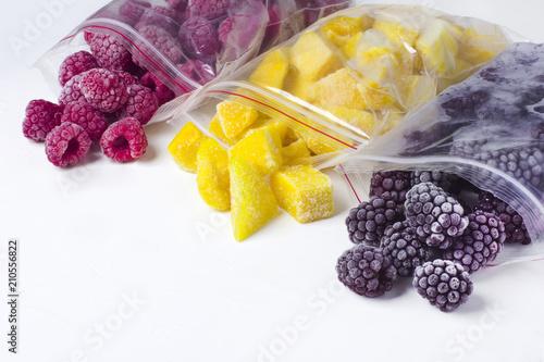 Obraz Frozen berries in reusable plastic bags: raspberry, mango and blackberry. White background - fototapety do salonu