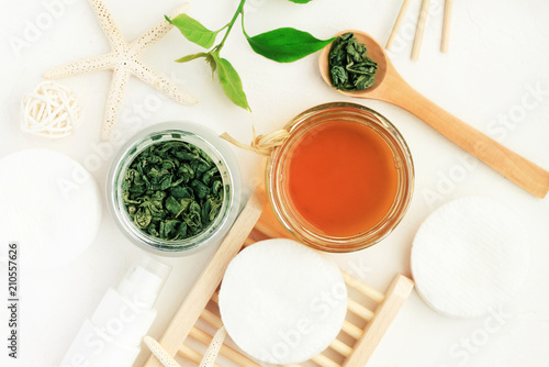 Cosmetic inredients with green tea extract for skincare. Homemade facial refreshing herbal tonic. Top view white table morning facial cleansing set.