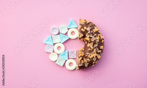Valokuva  hard candy and chocolade donut on pink background. Above view